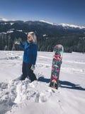 Muchacha rubia hermosa del Snowboarder en chaqueta azul con su tablero que se coloca en nieve en las montañas Imágenes de archivo libres de regalías
