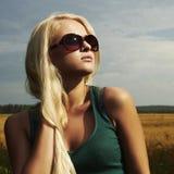 Muchacha rubia hermosa en el field.beauty woman.sunglasses Foto de archivo