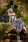Muchacha rubia hermosa en el fondo de la cascada Fotografía de archivo