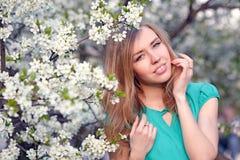 Muchacha rubia hermosa en el fondo de las flores blancas Imágenes de archivo libres de regalías