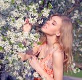 Muchacha rubia hermosa en el fondo de las flores blancas Fotografía de archivo