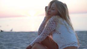 Muchacha rubia hermosa en la playa mira el mar y la cámara shooted sobre hora de oro cara emocional en la playa metrajes