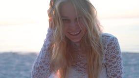 Muchacha rubia hermosa en la playa mira el mar y la cámara shooted sobre hora de oro cara emocional en la playa almacen de metraje de vídeo