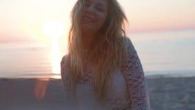 Muchacha rubia hermosa en la playa mira el mar y la cámara shooted sobre hora de oro cara emocional en la playa almacen de video