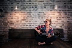 Muchacha rubia hermosa en la ropa causal que juega música en la guitarra imagenes de archivo