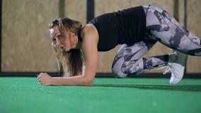 Muchacha rubia hermosa en las polainas grises que hacen el tablón en el gimnasio, ajuste del ejercicio de la cruz almacen de metraje de vídeo
