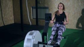 Muchacha rubia hermosa en las polainas grises que hacen un ejercicio en el gimnasio en un aparato de remar almacen de metraje de vídeo