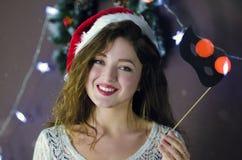 Muchacha rubia hermosa en sombrero de la Navidad en fondo de las decoraciones de la Navidad foto de archivo