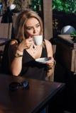 Muchacha rubia hermosa en un café en la calle Foto de archivo