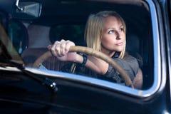 Muchacha rubia hermosa en un coche negro de la vendimia. Imagen de archivo