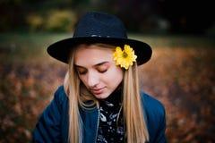 Muchacha rubia hermosa en un sombrero y en chaqueta azul con la flor amarilla en parque del otoño por completo de hojas amarillas imagenes de archivo
