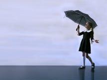 Muchacha rubia hermosa en un uniforme escolar en la lluvia Foto de archivo libre de regalías