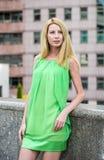 Muchacha rubia hermosa en un vestido corto verde del verano en las calles de la ciudad Foto de archivo