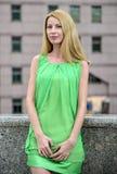 Muchacha rubia hermosa en un vestido corto verde del verano en las calles de la ciudad Fotos de archivo libres de regalías