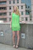 Muchacha rubia hermosa en un vestido corto verde del verano en las calles de la ciudad Foto de archivo libre de regalías