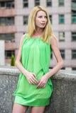Muchacha rubia hermosa en un vestido corto verde del verano en las calles de la ciudad Imagen de archivo