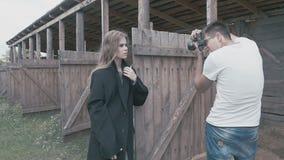 Muchacha rubia hermosa en una capa negra que presenta para el fotógrafo metrajes