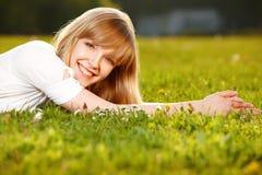 Muchacha rubia hermosa en una hierba Foto de archivo