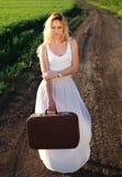 Muchacha rubia hermosa en vestido blanco largo con la maleta fotografía de archivo libre de regalías