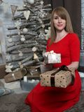 Muchacha rubia hermosa en vestido rojo y presentes del Año Nuevo Humor e interior del Año Nuevo Fotos de archivo