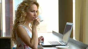 Muchacha rubia hermosa en vestido usando el ordenador portátil en café La mujer joven bebe el café y el trabajo en el cuaderno metrajes