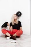 Muchacha rubia hermosa joven con el baloon negro en el sombrero que se sienta en el café de consumición del piso sobre la pared b Imagen de archivo