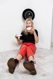 Muchacha rubia hermosa joven con el baloon negro en el sombrero que se sienta en el café de consumición del piso sobre la pared b Fotos de archivo libres de regalías