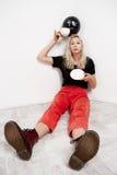 Muchacha rubia hermosa joven con el baloon negro en el sombrero que se sienta en el café de consumición del piso sobre la pared b Imágenes de archivo libres de regalías