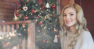 Muchacha rubia hermosa joven con el pelo rizado que sonríe y que mira el árbol de navidad almacen de video
