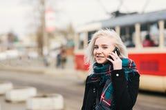 Muchacha rubia hermosa joven llevando caliente eso que habla en el teléfono en el fondo del paisaje urbano Fotos de archivo