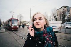 Muchacha rubia hermosa joven llevando caliente eso que habla en el teléfono en el fondo del paisaje urbano Fotos de archivo libres de regalías