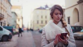 Muchacha rubia hermosa joven que camina abajo del camino solitario usando un app móvil en su smartphone por la mañana metrajes