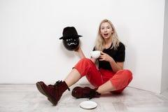 Muchacha rubia hermosa joven que lleva a cabo el baloon negro en el sombrero que se sienta en el café de consumición del piso sob foto de archivo libre de regalías