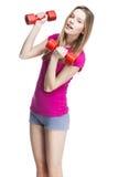 Muchacha rubia hermosa joven que lleva a cabo pesas de gimnasia Imágenes de archivo libres de regalías