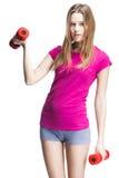 Muchacha rubia hermosa joven que lleva a cabo pesas de gimnasia Imagen de archivo libre de regalías