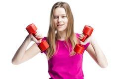 Muchacha rubia hermosa joven que lleva a cabo pesas de gimnasia Fotos de archivo libres de regalías