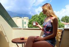 Muchacha rubia hermosa joven que se sienta en el balcón temprano por la mañana y el café de consumición y que come maduro rojo Fotografía de archivo