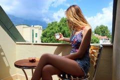 Muchacha rubia hermosa joven que se sienta en el balcón temprano por la mañana y el café de consumición y que come maduro rojo Imagenes de archivo