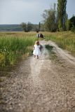 Muchacha rubia hermosa que corre abajo del camino Imagenes de archivo