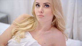 Muchacha rubia hermosa que miente en cama almacen de video