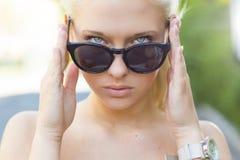 Muchacha rubia hermosa que mira sobre sus gafas de sol Fotografía de archivo libre de regalías