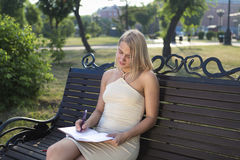 Muchacha rubia hermosa que se sienta en el parque que toma abajo de notas importantes imagen de archivo libre de regalías