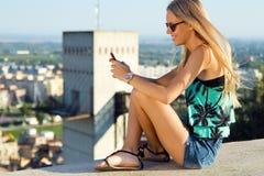 Muchacha rubia hermosa que se sienta en el tejado con el teléfono móvil Fotografía de archivo libre de regalías