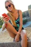 Muchacha rubia hermosa que se sienta en el tejado con el teléfono móvil Fotos de archivo