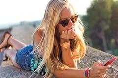 Muchacha rubia hermosa que se sienta en el tejado con el teléfono móvil Foto de archivo libre de regalías