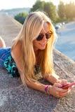 Muchacha rubia hermosa que se sienta en el tejado con el teléfono móvil Imagen de archivo libre de regalías