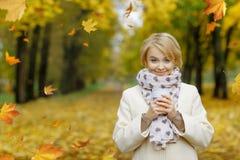 Muchacha rubia hermosa que sostiene la taza de té caliente en otoño hermoso Imagen de archivo