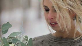 Muchacha rubia hermosa que sostiene un ramo en bosque del invierno almacen de video
