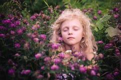 Muchacha rubia hermosa que sueña entre las flores Imagen de archivo libre de regalías