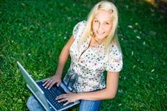 Muchacha rubia hermosa que usa la computadora portátil en naturaleza. Fotografía de archivo